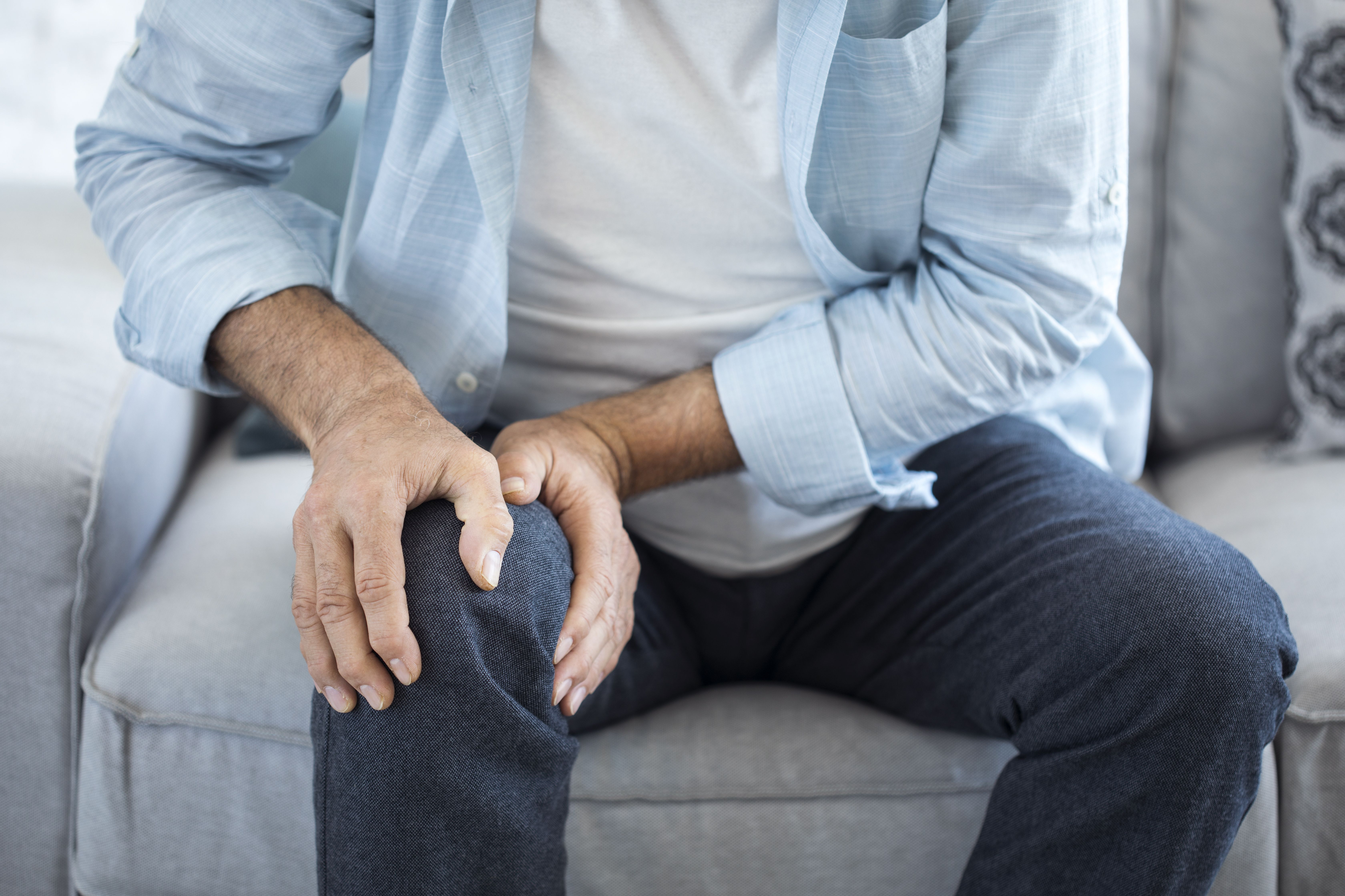 man with hands cupped around right knee